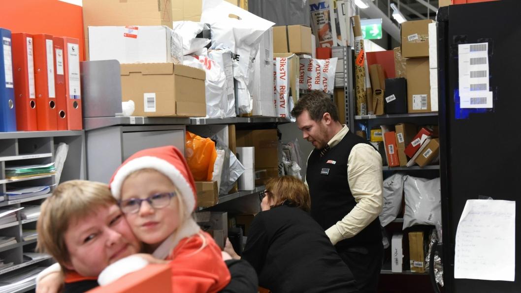 Hyllene fylles opp, og butikksjefen ber kundene hente pakkene raskt etter de har mottatt varsel. Her er Eirin Karlsen med Cornelia Celin Dahl (5) på armen. Bak: postansvarlig Marit Storsveen og butikksjef Arnt Christoffer Weberg Schjong. FOTO: Birger Morken / Posten