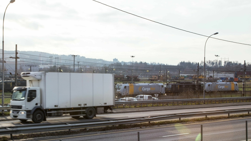 På Alnabru står symptomatisk nok en lang rekke CargoNet-lokomotiver stille, mens lastebilene suser forbi på Østre Aker Vei.