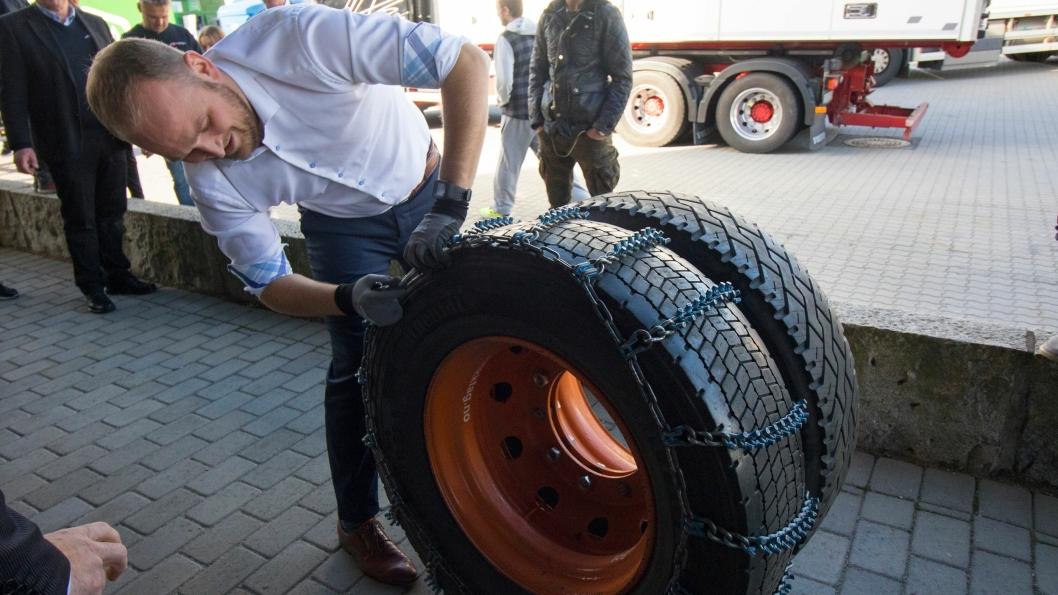 Samferdselsminister Jon Georg Dale vil ha strengere regler for vinterdekk på tunge kjøretøy. Her tester han ut å legge på kjetting.