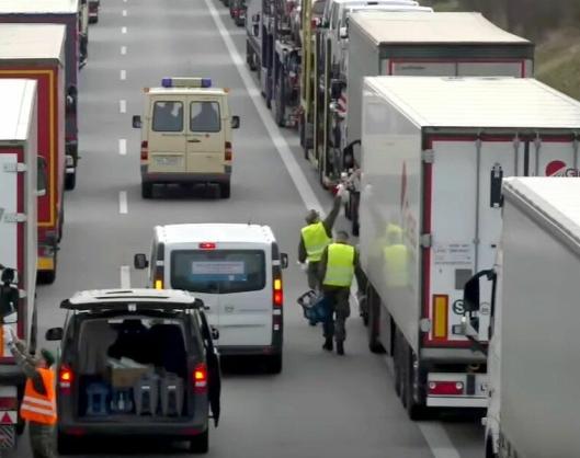 Tyske militære og Røde Kors deler ut mat og drikke til sjåførene i hundrevis av vogntog i kø i Tyskland ved grensen mot Polen 19. mars.