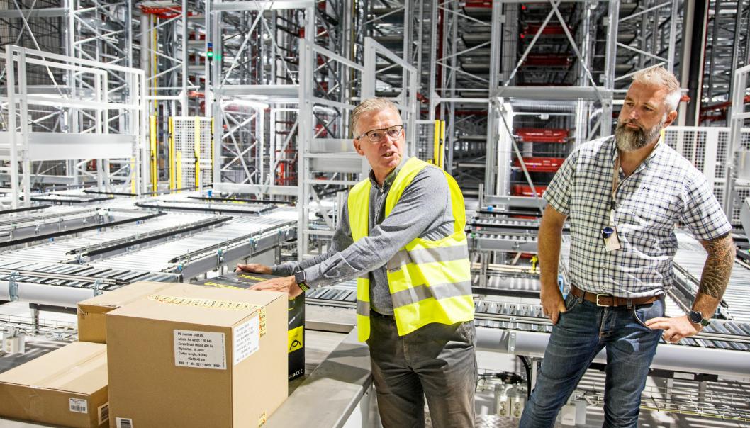 HER SKJER MAGIEN: Logistikkdirektør i Europris Pål Christian Andersen (til venstre) sammen med Swisslogs prosjektleder Øystein Araldsen, ved en av seks plukkstasjoner for plukking av ordrepall.