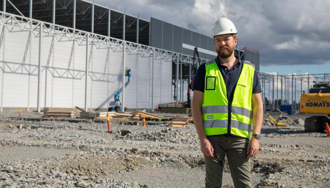 Audun Tharaldsen, logistikksjef i Optimera, foran bygget under oppføring.