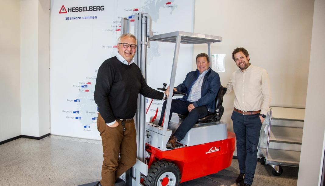 FORNØYD GJENG: Administrerende direktør Per Erik Pedersen (fra venstre), Kai Paulshus, som var med helt fra starten, og konserndirektør Andreas Corwin gleder seg over 20 år suksess i truckmarkedet. Paulshus sitter på en Linde-truck fra 1977 som står i foajeen i Hesselbergs flotte nybygg på Lindeberg.