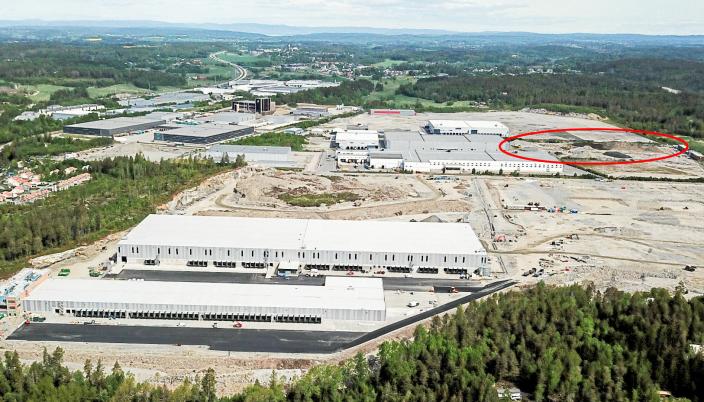 Dette dronebildet av DSVs anlegg (de to byggene i forkant) ble tatt i fjor, og mye er skjedd siden da. Det nye bygge skal føres opp der den rød ringen markerer.
